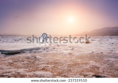Beautiful winter landscape with ice and snow on the lake at sunset. Small depth of sharpness. Vintage filter - stock photo