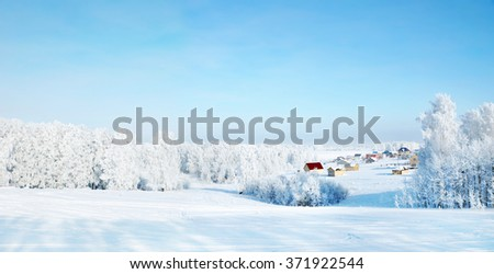 Beautiful winter landscape with rural houses and woods covered with hoarfrost - stock photo