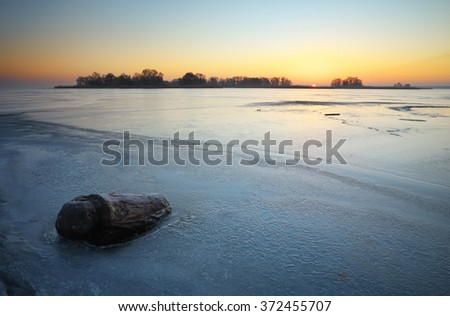 Beautiful winter landscape with stump in the ice and sunset sky.