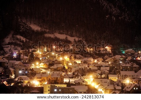 Beautiful winter night scene with old houses covered in snow near a forest