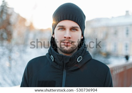 Beautiful winter portrait of a handsome man in a knitted hat at sunset