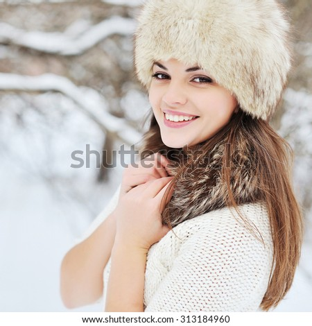 Beautiful winter portrait of young woman in fur hat - stock photo