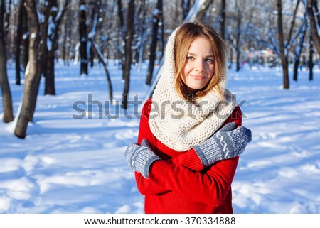 Beautiful winter portrait of young woman in red sweaterin winter snowy  park