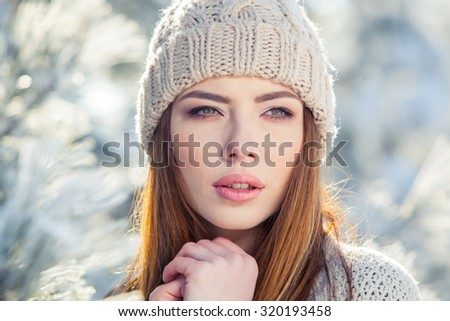 Beautiful winter portrait of young woman in the winter snowy scenery. - stock photo