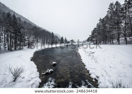 Beautiful winter scenery by the lake and the River. Heavy snow and blizzard is giving the scenery a unique appearance and look. Frozen river and rocks on the coast. - stock photo