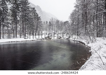 Beautiful winter scenery by the lake and the River. Heavy snow and blizzard is giving the scenery a unique appearance and look. Hills hidden in fog behind. - stock photo