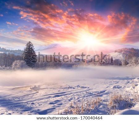 Beautiful winter sunrise in the mountain village. - stock photo