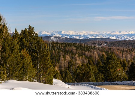 Beautiful winter top view on the mountains covered with dense forest and snow on background of snowy mountains and blue sky  - stock photo