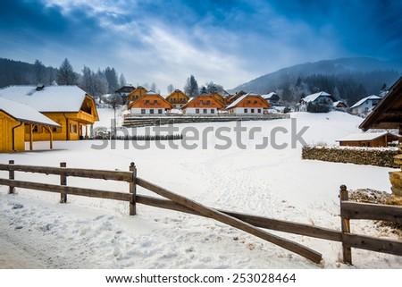 Beautiful winter view of farm on mountain at Austrian town - stock photo