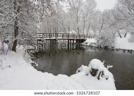 Beautiful winter view on the Yauza river and wooden bridge after heavy snowfall in Moscow, Babushkinkiy district.