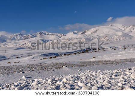 Beautiful winter views of the mountains covered with snow and snowy valley with sparse vegetation on a background of blue sky and clouds - stock photo