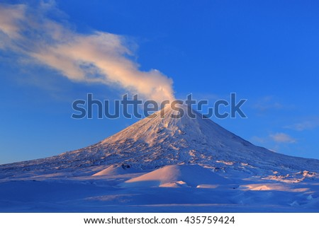 Beautiful winter volcanic landscape of Kamchatka Peninsula: view of eruption active Klyuchevskoy Volcano at sunrise. Eurasia, Russia, Far East, Kamchatka Region, Klyuchevskaya Group of Volcanoes. - stock photo