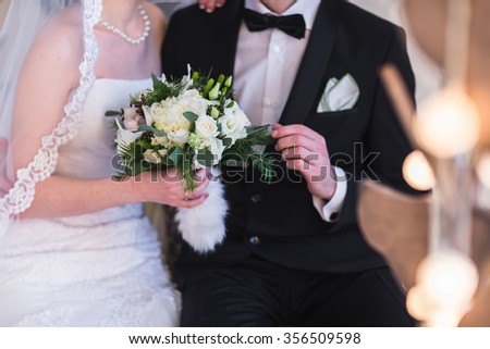 Beautiful winter wedding bouquet. Bridal bouquet with cones, cotton and spruce branches. The bride holds a wedding bouquet next to the groom. - stock photo