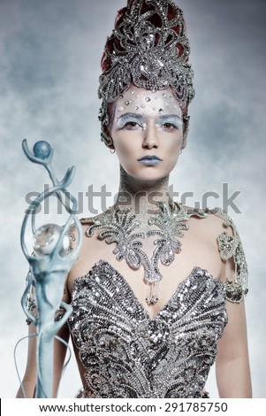 Beautiful winter witch in silver dress - stock photo