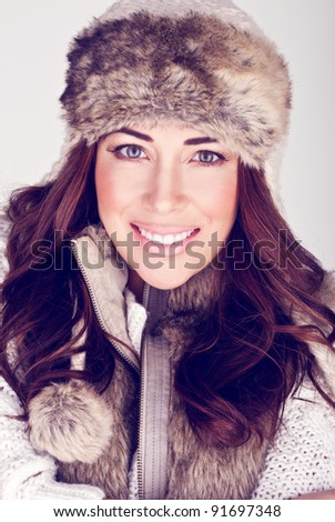 Beautiful Winter Woman In Subtle Make-up. Beauty shot of a beautiful smiling woman with clear complexion and subtle make-up wearing winter fur hat and ensemble. - stock photo