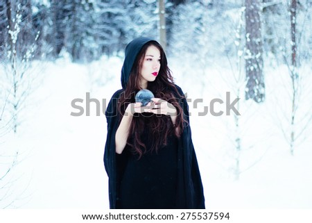 Beautiful witch in black cloak with magi? ball - stock photo
