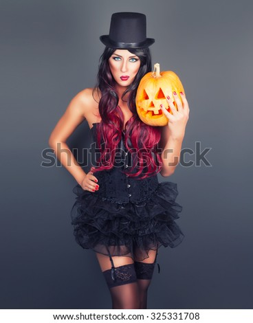 Beautiful witch in black gothic Halloween costume holding Jack-o-lantern in hands - stock photo