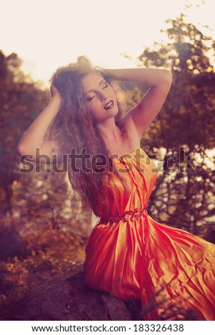 Beautiful witch in the woods near the fire. Magic woman celebrating Halloween. Girl doing witchcraft in the forest. - stock photo