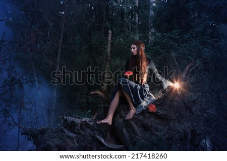 Beautiful witch sitting on a tree trunk in the forest - stock photo