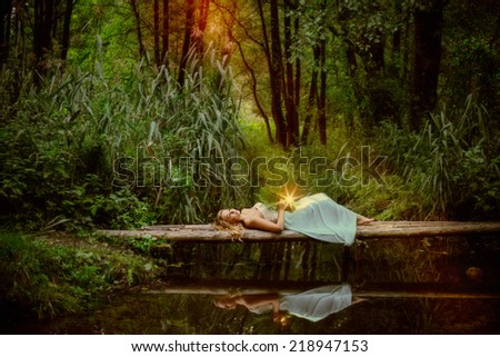 beautiful witch sitting on wooden bridge over the river and practice witchcraft