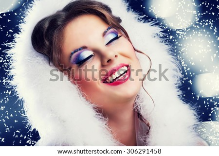 beautiful woman against blue background with snowflakes, Christmas topic - stock photo