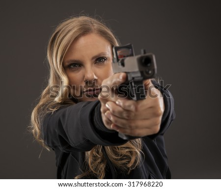 Beautiful woman aiming gun. - stock photo
