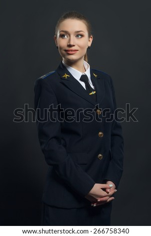 beautiful woman airline pilot with arms crossed - stock photo