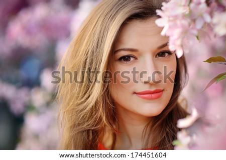 Beautiful woman among spring blossom. - stock photo