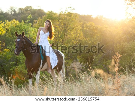 Beautiful woman and a horse. Summer time - stock photo