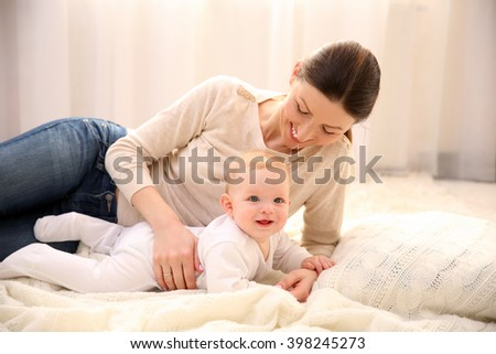 Beautiful woman and cute baby lying on the floor