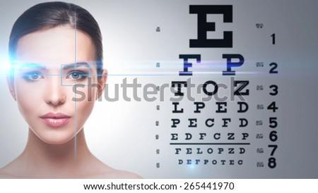 Beautiful woman and eye chart on background - stock photo