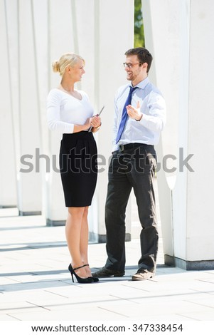 Beautiful woman and handsome man being business partners outside.
