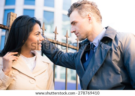 Beautiful woman and handsome man flirting outdoors - stock photo