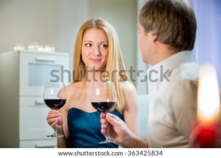 Beautiful woman and handsome man having romantic dinner with candles at home. Couple celebrating Valentines day - stock photo