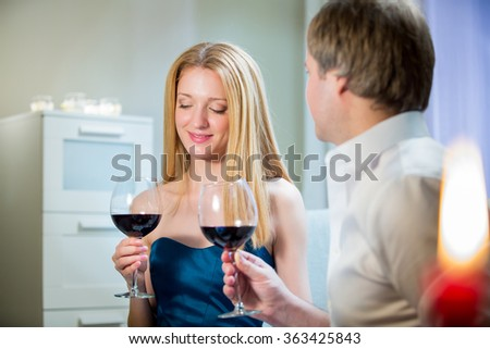 Beautiful woman and handsome man having romantic dinner with candles at home. Couple celebrating Valentines day