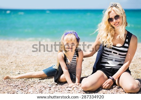 Beautiful woman and her charming daughter resting on the sea - stock photo