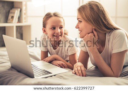 Beautiful woman and her cute little daughter are using a laptop and smiling while lying on bed