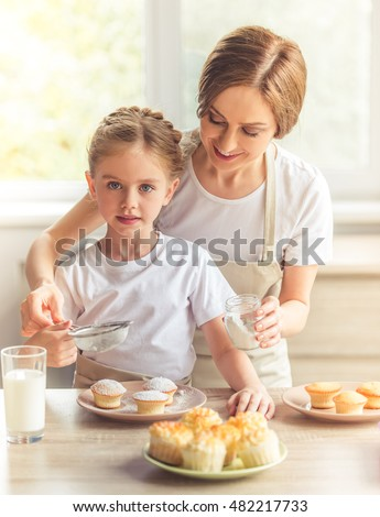 Beautiful woman and her cute little daughter in aprons are smiling while dredging muffins with sugar powder