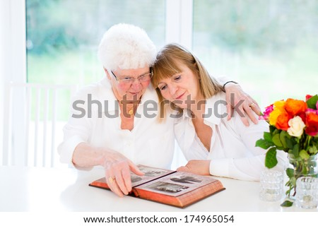 Beautiful woman and her loving mother watching together a black and white photo album in a white sunny living room - stock photo
