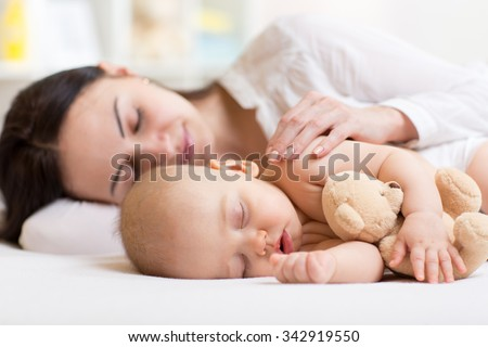 beautiful woman and her son little baby sleeping together in a bedroom - stock photo