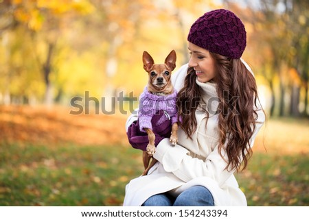 beautiful woman and his dog in autumn park - stock photo