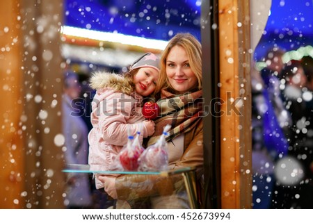 Beautiful woman and little daughter eating crystalized sugared apple on German Christmas market. Happy family in winter clothes with lights on background. Family, tradition, holiday concept - stock photo