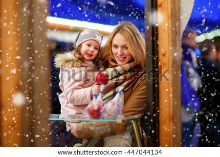 Beautiful woman and little kid girl eating crystallized sugared apple on German Christmas market. Happy family in winter clothes with lights on background. Family, tradition, holiday concept - stock photo