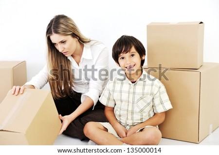 Beautiful woman and little smiling child openig cardboard box - stock photo