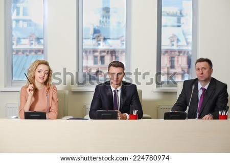 Beautiful woman and two men in suits sitting in a row at the table in the office - stock photo