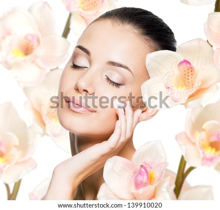 Beautiful woman applying cosmetic cream  on face with flowers. Skin care concept. - stock photo