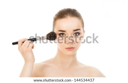 beautiful woman applying cosmetic with brush