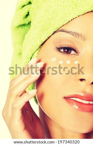 Beautiful woman applying cream on face - stock photo