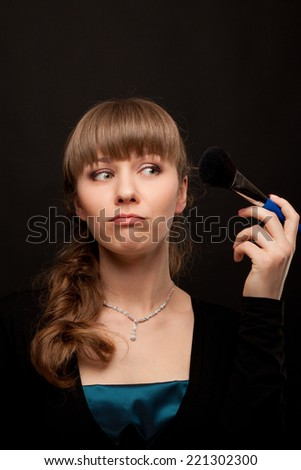 Beautiful woman applying her make up by powder bruh - stock photo