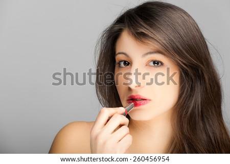 Beautiful woman applying lipstick - stock photo